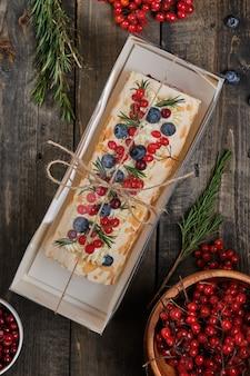Silvester-baiser-rolle mit erdbeeren, heidelbeeren, himbeeren und preiselbeeren