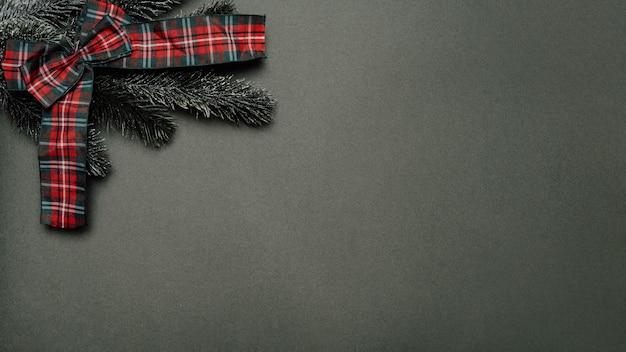 Silvester-flatley. weihnachtsbaumaste und ein bogen auf einem festen grünen hintergrund. leerer platz für ihre anzeige oder ihren text.