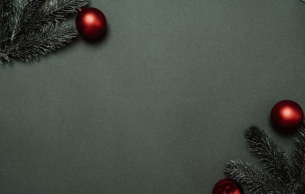 Silvester-flatley. weihnachtsbaumaste und luftballons auf einem einfarbigen grünen hintergrund. leerer platz für ihre anzeige oder ihren text.