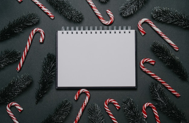 Silvester-flatley. weihnachtstannenzweige, kegel, kugeln und karamellschilf auf einem einfarbigen grünen hintergrund. leerer platz für ihre anzeige oder ihren text.