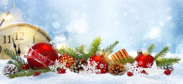 Silvester-komposition. uhr im retro-stil mit tannenzweigen, zapfen, dekorationen und geschenken auf schneehintergrund. letzte momente vor weihnachten oder neujahr