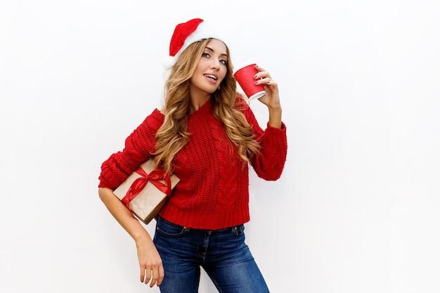 Silvester- oder heiligabendstimmung. blondes attraktives mädchen im maskeradenhut, der geschenkboxen hält freudige stimmung.
