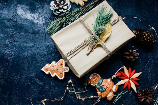 Silvesteratmosphäre neujahrsgeschenk und eine kerze stehen neben dem weihnachtsbaum und weihnachtsspielzeug auf dunklem hintergrund