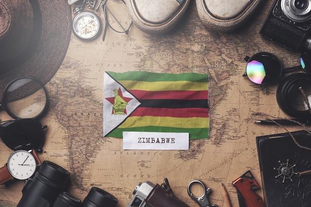 Simbabwe-flagge zwischen dem zubehör des reisenden auf alter weinlese-karte. obenliegender schuss