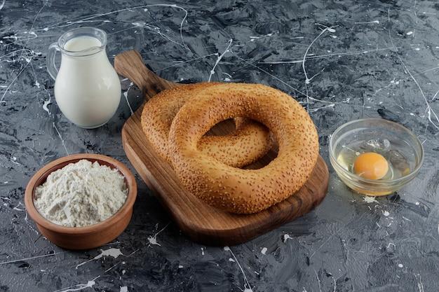 Simit mit sesam und einer glasschüssel mehl mit ungekochtem hühnerei