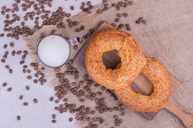 Simit rollt auf holzbrett mit einem glas getränk und kaffeebohnen herum.
