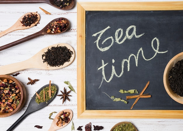 Simsen sie den teekalk, der auf schiefer mit verschiedenen arten von kräutern auf hölzernem schreibtisch geschrieben wird