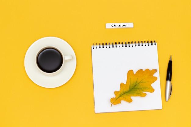 Simsen sie oktober-kaffeetasse, offenen notizblock mit stift und gelbes eichenblatt auf gelbem hintergrund.
