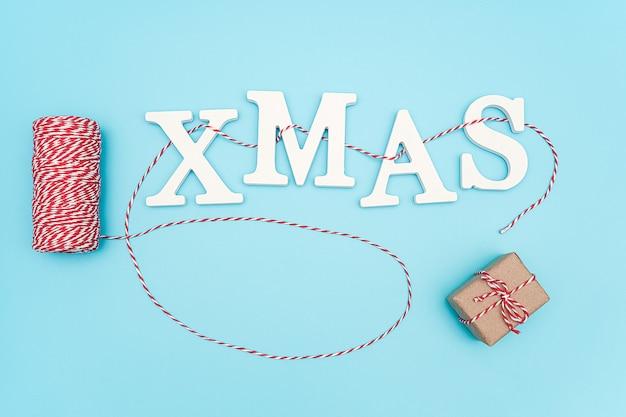 Simsen sie weihnachten von den weißen volumenbuchstaben auf roter und weißer schnur und geschenkbox der weihnachtsdekoration auf blauem hintergrund.