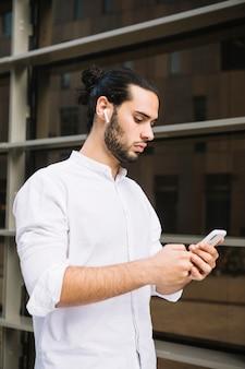 Simsende mitteilung des stilvollen geschäftsmannes auf smartphone an draußen