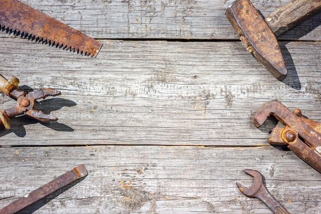 Sind die werkzeuge auf hölzernen hintergrundhammerzangen und -schlüssel