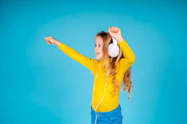 Singe glück. glückliches kind tragen kopfhörer. kleiner musikfan. glückliches kleines mädchen. kleines mädchen hören isoliert musik. genieß es.