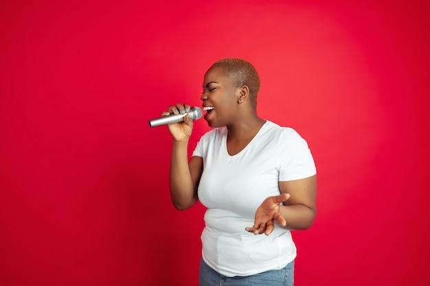 Singen inspiriert. porträt einer afroamerikanischen jungen frau auf rot