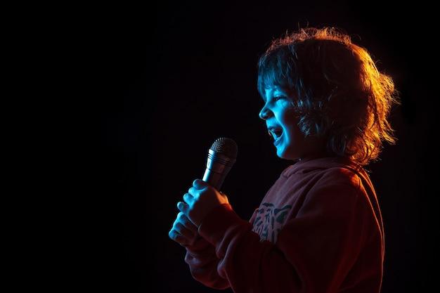 Singen wie berühmtheit, rockstar. porträt des kaukasischen jungen auf dunklem studiohintergrund im neonlicht. schönes lockiges modell. konzept der menschlichen emotionen, gesichtsausdruck, verkauf, werbung, musik, hobby, traum.