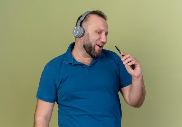 Singender erwachsener slawischer mann, der kopfhörer mit handy als mikrofon trägt