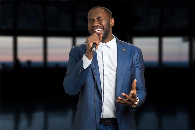 Singender mann am abend. dunkelhäutiger mann mit mikrofon. schwarzer mann singt mit geschlossenen augen und leidenschaft.