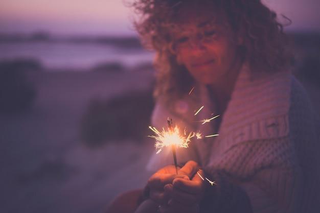 Single attraktive frau defokussiert porträt allein funkelt ein feuerwerk, um neujahr oder party im freien auf alternative weise ohne freunde zu feiern - trauriges und glückliches konzept