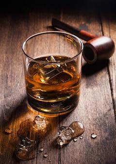 Single malt scotch whisky in klassischem glas mit eiswürfeln und pfeife
