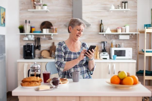 Single senior woman surfen am telefon in der küche während des frühstücks. authentische ältere person mit moderner smartphone-internettechnologie, die im rentenalter freizeit mit gadget genießt