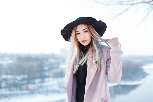 Sinnlich schöne junge frau mit blonden haaren in einem vintage-hut in einem winterrosa mantel im retro-stil steht draußen
