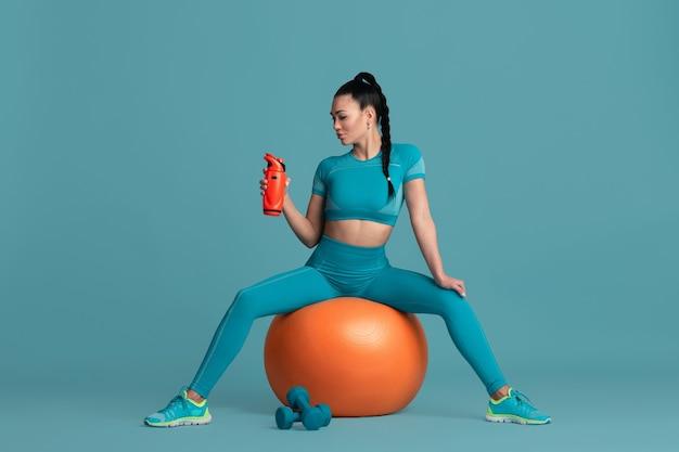 Sinnlich. schöne junge sportlerin üben, einfarbiges blaues porträt. sportliches fittes brunettemodell mit fitball bodybuilding, gesunder lebensstil, schönheits- und aktionskonzept.