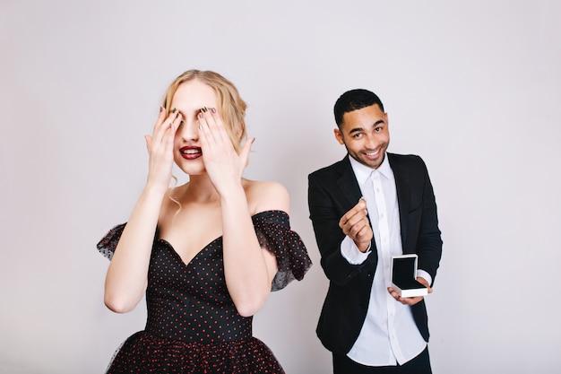 Sinnlich schöne momente der jungen frau im luxuskleid mit geschlossenen augen, die auf überraschung vom gutaussehenden mann mit ring warten. valentinstag feiern, liebhaber, geschenk.