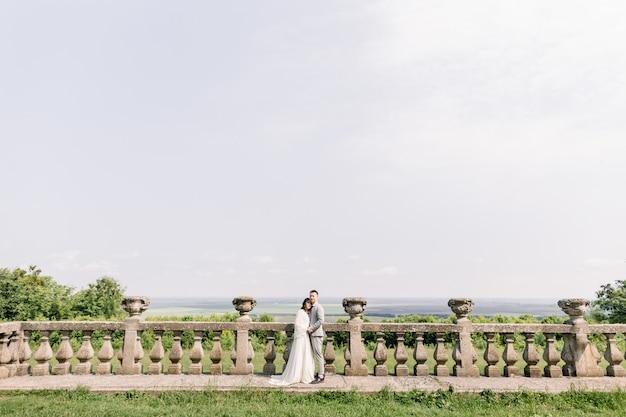 Sinnlich verheiratetes asiatisches paar, frau und mann, umarmend vor altem slawischen schloss