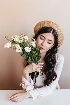 Sinnliche asiatische frau, die weiße eustomas schnüffelt. studioaufnahme der hübschen chinesischen frau, die blumenstrauß hält.