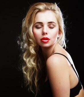 Sinnliche blonde frau mit lockigem haar in schwarzen dessous, nahaufnahme