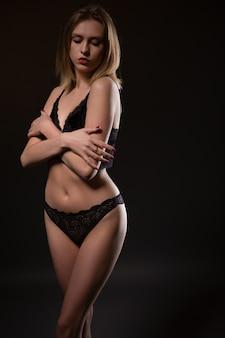 Sinnliche blondine, die in der schwarzen unterwäsche auf einer dunklen wand aufwirft.