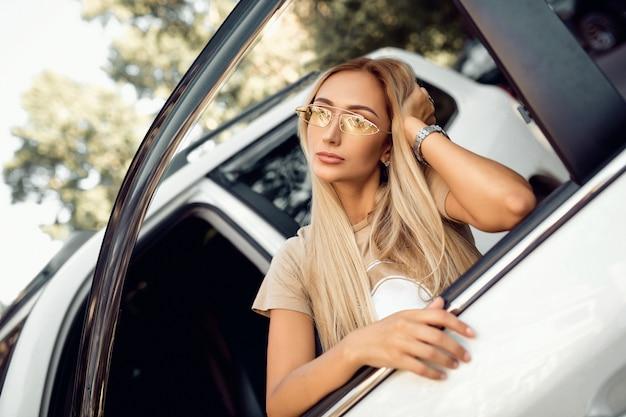 Sinnliche blondine in stilvoller kleidung, die in einem schönen auto aufwirft. autos und mädchen