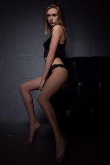 Sinnliche blondine posiert in schwarzer unterwäsche auf dunkler oberfläche. studioaufnahme