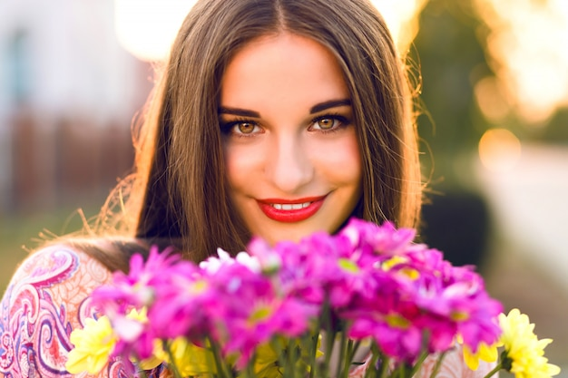 Sinnliche brünette frau, die mit blumenstrauß nach romantischem datum, sonnenuntergangsfarben, elegantem kleid und make-up aufwirft.