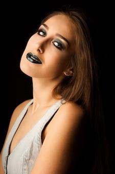 Sinnliche brünette frau mit perfekter haut und kreativem metallisch-grünem make-up. nahaufnahmeportrait im studio auf dunklem hintergrund
