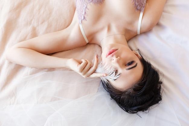 Sinnliche brunetteschönheit, die auf bett im weißen wäscheabdeckungsauge mit feder liegt