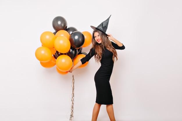 Sinnliche frau im hexenkostüm, das auf halloween wartet und orangefarbene luftballons hält