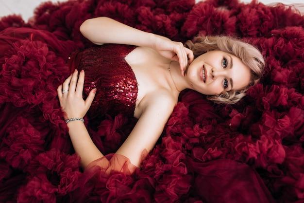 Sinnliche frau im roten burgundi-kleid liegt auf dem boden im hellen raum