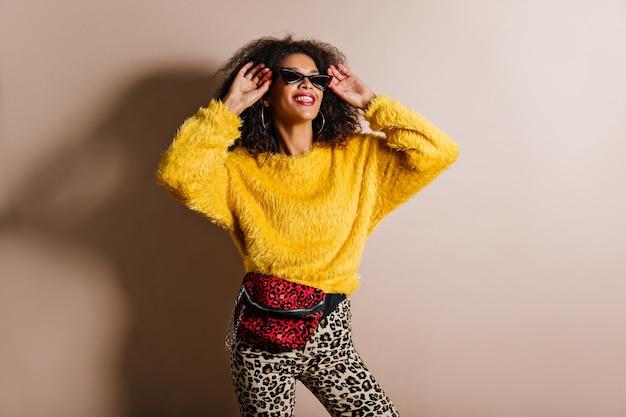 Sinnliche frau im trendigen gelben pullover, der oben schaut
