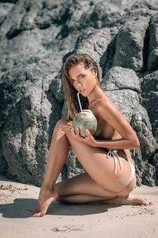 Sinnliche frau im weißen bikini, der kokosmilch trinkt
