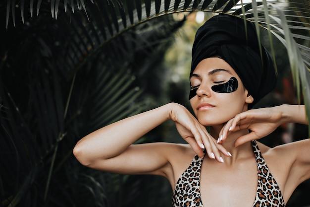 Sinnliche frau mit augenklappen, die unter palme stehen. schöne frau im turban, der auf naturhintergrund aufwirft.