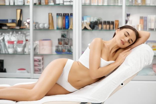 Sinnliche frau mit der schlanken figur, die im spa-salon entspanntes weißes höschen und handtuch-bh entspannt