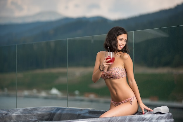 Sinnliche frau mit perfektem körper im bikini, der am jacuzzi mit cocktail sitzt und weg gegen unscharfen hintergrund der natur schaut