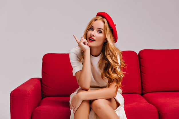 Sinnliche frau mit roten lippen, die auf couch sitzen. erstauntes französisches weibliches modell in der baskenmütze, die zeit im wohnzimmer verbringt.