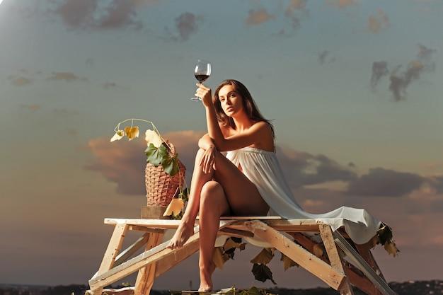Sinnliche frau mit rotweinglas-weidenflasche und weinstock auf abendnatur über dramatischem himmel