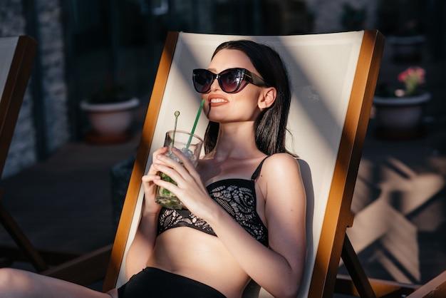 Sinnliche frau mit sonnenbrille ein cocktail trinkend