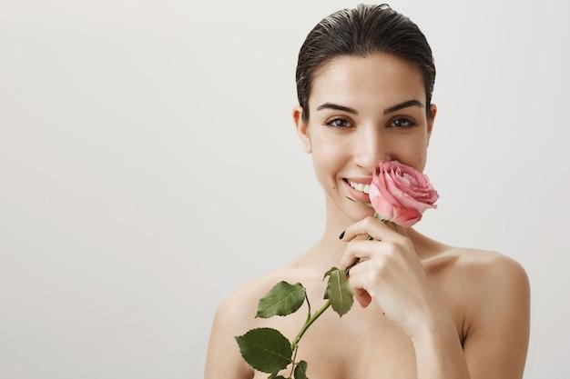 Sinnliche glückliche frau, die nackt mit rose steht und flirtend lächelt