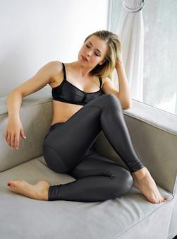 Sinnliche hübsche blonde frau, die auf sofa aufwirft, sportlich und gesund.