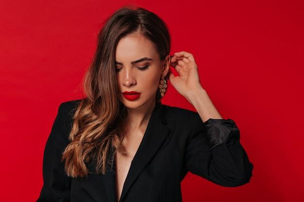 Sinnliche hübsche frau mit roten lippen, die goldene ohrringe und schwarze jacke tragen, die über roter wand aufwirft