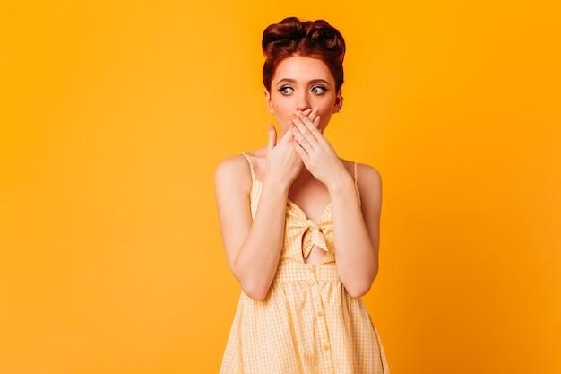 Sinnliche ingwerfrau, die mund mit händen bedeckt. studioaufnahme des trendigen weiblichen pinup-modells lokalisiert auf gelbem raum.