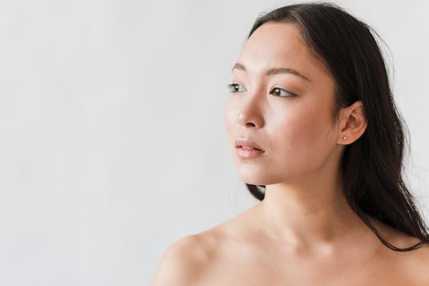 Sinnliche junge asiatische frau, die schulterfrei steht